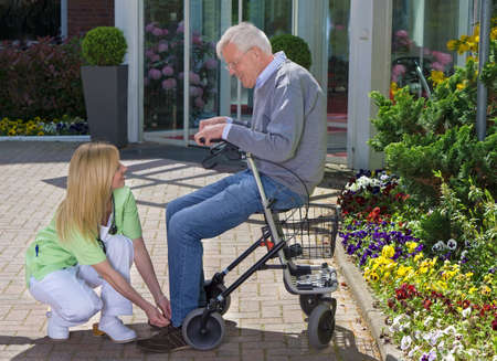 mobility nursing: Smiling Blond Nurse Helping Senior Man with Walker to Tie Shoe Laces Outdoors in front of Retirement Building on Sunny Day near Garden