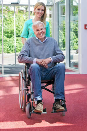 mobility nursing: Portrait of Smiling Blond Nurse Pushing Senior Man in Wheelchair Through Lobby of Building
