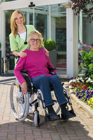 eldercare: Portrait of Smiling Blond Nurse Standing Behind Senior Woman in Wheelchair Outdoors in front of Building on Sunny Day