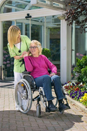Blond Nurse Standing Behind Senior Woman in Wheelchair with Hand on Shoulder Outdoors in front of Building on Sunny Day Stock Photo