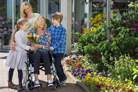 silla de ruedas: Tiempo de la familia preciosa juntos en el aire fresco Foto de archivo
