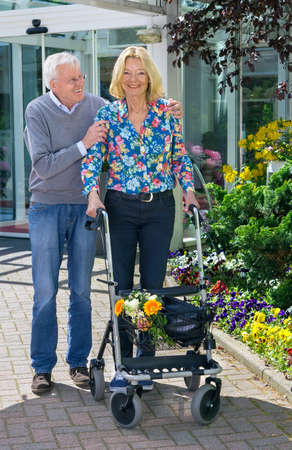 mobility nursing: Senior Man Helping Blond Woman with Walker Walking Outdoors in front of Retirement Community Building on Sunny Day