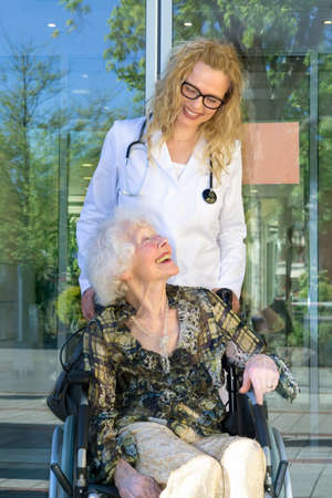 Hospital care: Happy Female Heath Care Assistant and Elderly Woman Patient Sitting on Wheelchair Outside the Hospital.