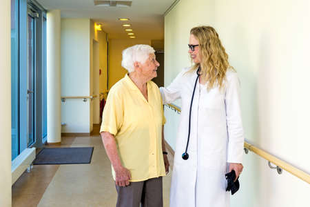 Attractive female doctor chatting to an elderly lady patient in a hospital corridor reassuring her with a smile and a hand on her back