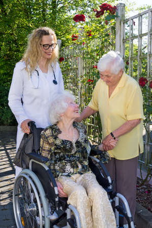 special needs: Young Female Doctor and Middle Aged Caregiver Caring an Elderly Woman with Special Needs on Wheelchair at the Garden Outside Nursing Home.