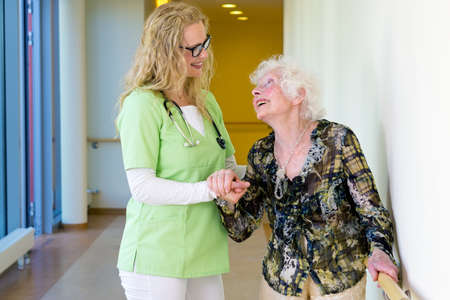 frail: Kind Therapist Woman Assisting an Elderly Patient with Special Needs Walking at the Corridor Inside the Hospital