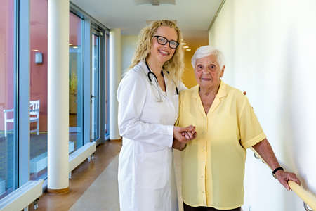 mobility nursing: Young Female Nurse and her Elderly Woman Patient Smiling at the Camera While Standing at the Hallway Inside the Nursing Home.