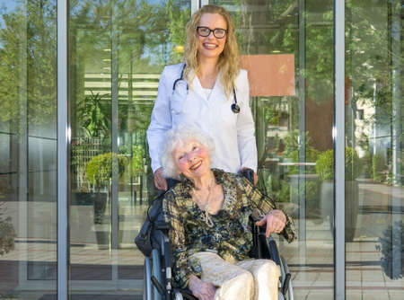 paralysis: Happy Young Female Nurse and Elderly Woman Patient on Wheelchair Smiling at the Camera Against Hospital Glass Doors. Stock Photo