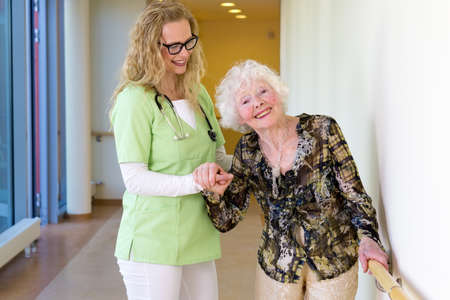 ageing: Kind Young Medical Assistant Assisting a Happy Elderly Woman Patient Walking at the Corridor in the Hospital.