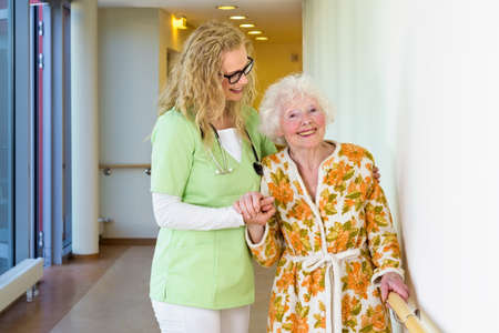 medical assistant: Young Female Medical Assistant Helping a Happy Old Woman with Special Needs Walking in the Hospital Corridor While Smiling at the Camera.