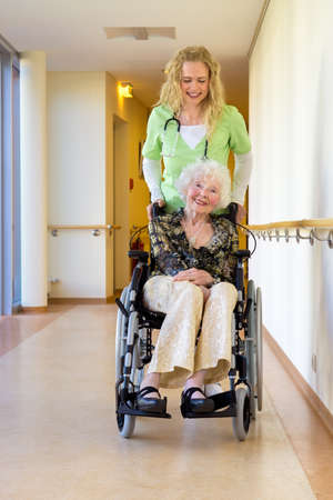 special needs: Young Female Medical Assistant Assisting an Elderly Woman with Special Needs on a Wheelchair at the Hospital Corridor