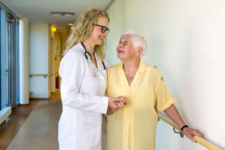 special needs: Happy Medical Assistant Assisting an Elderly Woman with Special Needs at the Corridor Inside the Hospital
