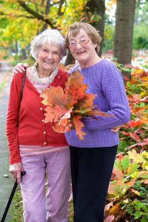 elderly people: Two Senior Ladies at the Pathway  Holding Autumn Leaves and Looking at the Camera with Happy Facial Expression.