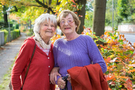 Half Body Shot of Two Happy Middle Aged Women in Autumn Outfits at the Pathway  Smiling at the Camera.