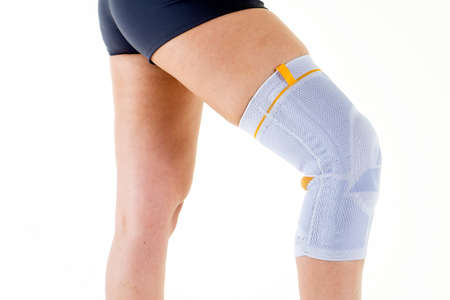 Primer plano de mujer con flexible Refuerzo ortopédico de apoyo elástico en la rodilla doblada en estudio con fondo blanco Foto de archivo