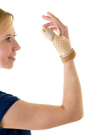 post operative: Waist Up Portrait of Smiling Young Blond Woman Looking at Camera and Wearing Supportive Thumb and Hand Brace in Studio with White Background