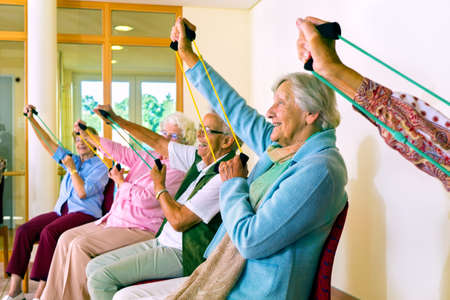 seated: Group of older women seated in chairs using stretching bands for physical fitness class