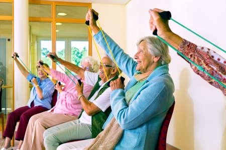 mujeres sentadas: Grupo de mujeres de edad sentado en las sillas que utilizan bandas de estiramiento para la clase de aptitud física Foto de archivo