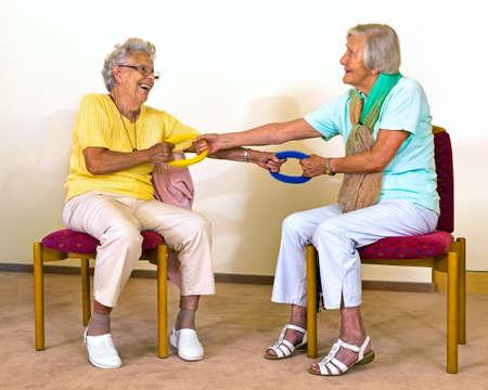 Twee gelukkige hogere vrouwen in stoelen beoefenen partner strekt zich met weerstand bands om kracht te verbeteren Stockfoto