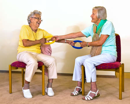 Two happy senior women in chairs practicing partner stretches with resistance bands to improve strength