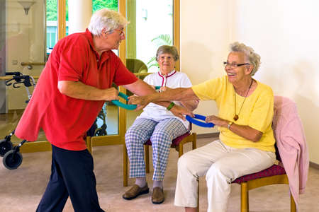elderly woman: Fitness trainer in red demonstrating with senior woman in class how to use resistance bands while seated Stock Photo