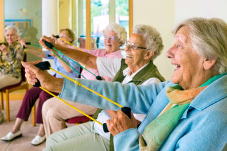 tercera edad: Gran grupo de felices señoras mayores entusiastas ejercicio en un gimnasio sentados en sillas haciendo ejercicios de estiramiento con bandas de goma
