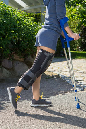 Young woman wearing an adjustable leg brace to support and immobilize her knee post operative, side view, walking outdoors on crutches in a garden