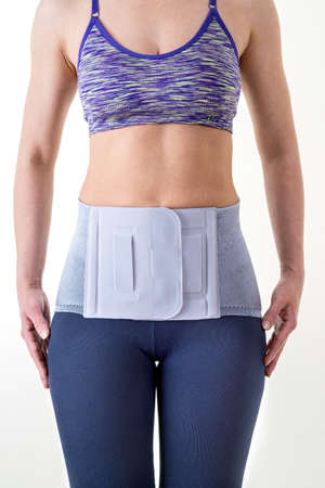stabilization: Close Up Front View of Athletic Woman Wearing Modern Orthopedic Lower Back Brace for Support Secured with Velco in Studio with White Background