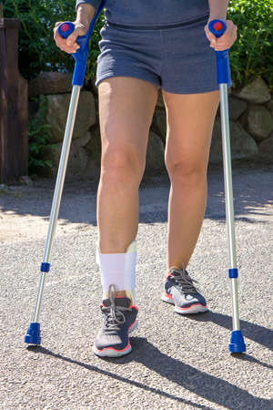 stabilization: Front Waist Down View of Person Wearing Shorts and Athletic Sneakers with Cast or Brace on Ankle and Walking with Crutches in Sunny Outdoor Environment