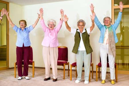 Gelukkig enthousiaste groep van senior vrouwen die een fysieke training in een sportschool senioren staan lachen en lachend met hun handen naar voren in de lucht Stockfoto