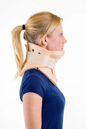 neck brace: Close Up Side Profile of Young Blond Woman with Hair in Ponytail in Blue T-Shirt and Wearing Neck Brace in Studio with White Background