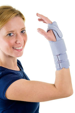 carpal tunnel syndrome: Waist Up Portrait of Smiling Young Blond Woman Looking at Camera and Wearing Supportive Wrist Brace in Studio with White Background