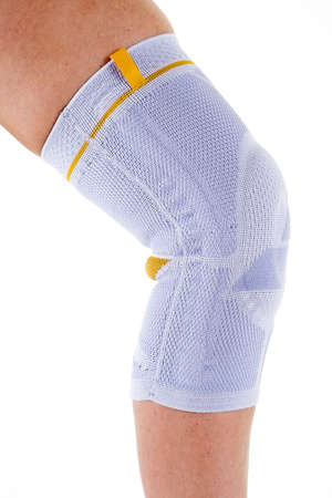kneecap: Close Up Side Profile View of Man Wearing Supportive Orthopedic Elastic Knee Brace on Leg in Studio with White Background