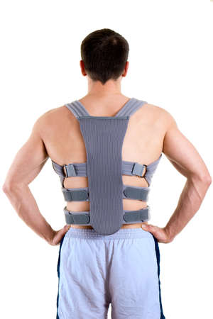 fractures: Rear View of Shirtless Man Wearing Athletic Shorts Standing with Hands on Hips and Wearing Padded Supportive Back Brace in Studio with White Background