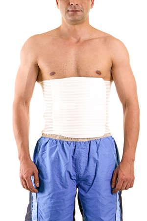 ortopedia: El hombre sin camisa en Studio con fondo blanco que lleva Refuerzo ortopédico de soporte del núcleo y la espalda baja