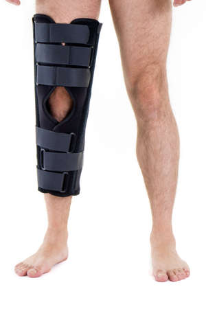 post operative: Detail of Lower Half of Man Wearing Supportive Leg Brace in Studio with White Background with Copy Space Stock Photo