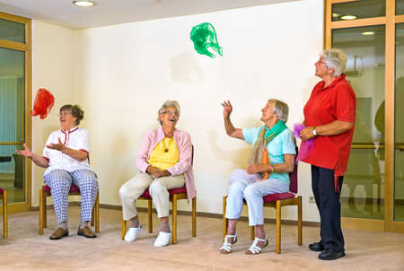 Happy elderly ladies in a gym sitting on chairs tossing colorful scarves into the air as a coordination exercise watched by an instructor