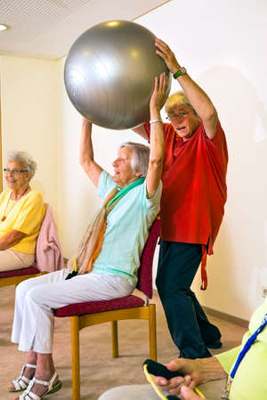 home trainer: Fitness trainer working with smiling senior woman lifting a silver stability ball for exercise at an old-age home
