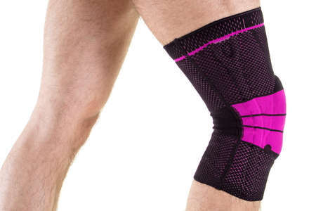 kneecap: Close Up Side View Profile of Man Wearing Flexible Elastic Orthopedic Knee Support Brace, in Bright Pink and Black Colors, in Studio with White Background