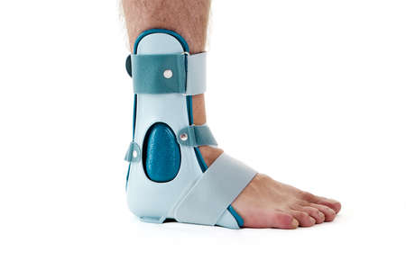 Close Up of Man Wearing Supportive Ankle Cast Brace, Secured by Velcro Straps, in Studio with White Background and Copy Space