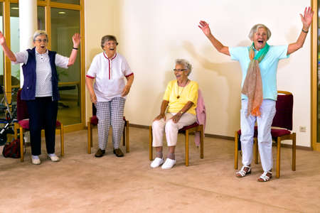 Group of four cheering senior women practicing light aerobic exercises with chairs for fitness class indoors