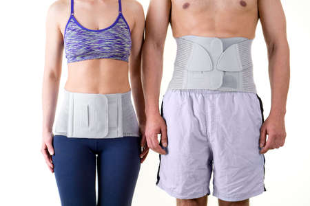 Detail of Mid Section of Athletic Man and Woman Wearing Supportive Orthopedic Back Braces for Lower Back, Standing Together in Studio with White Background