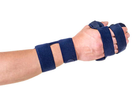 post operative: Close Up of Person with Velcro Straps Securing Supportive Hand and Wrist Brace in Studio with White Background