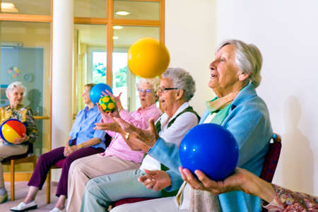grupos de personas: Grupo de señoras mayores felices que hacen ejercicios de coordinación en un gimnasio de la tercera edad sentados en sillas de lanzar y recoger las bolas de colores brillantes
