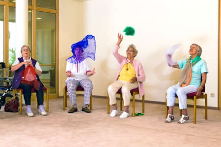 scarves: Senior ladies having fun while exercising at a seniors gym as they sit on chairs throwing colorful scarves in the air to improve coordination Stock Photo