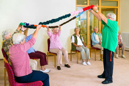 home trainer: Trainer in green shirt holding colorful garland aloft with group of senior women in fitness class at retirement home Stock Photo