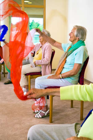 flicking: Small group of senior women using color fabric to improve arm mobility during an exercise class