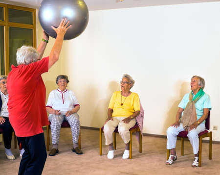 Elderly sports instructor working with senior ladies in a gym demonstrating exercises with the pilates ball as they watch from their chairs