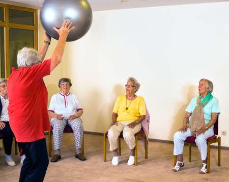 Ouderen sportinstructeur werken met senior dames in een sportschool aan te tonen oefeningen met de pilates bal als ze kijken uit hun stoelen