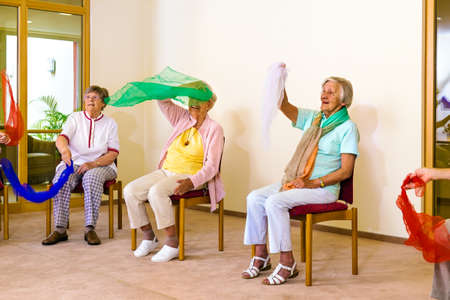 Group of excited senior women seated in chairs waving colorful scarves for physical fitness class indoors